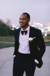 A man stands smiling in a tuxedo, his hands in his pockets.
