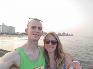 A selfie of a couple standing near the water, smiling.