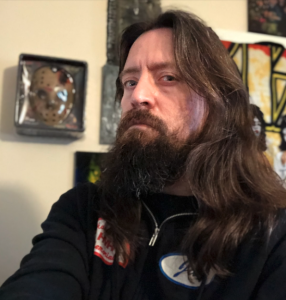 A man with long dark hair and a beard looks at the camera, unsmiling. He's wearing a black zip hoodie.