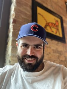 A bearded man in a Chicago Cubs hat smiles at the camera