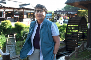 A woman with cropped grey hair and glasses, wearing a blue vest and short sleeve button down, stands in a garden