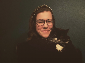 Tori smiling at the camera holding her cat named Rory, who is definitely not smiling.