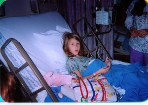 Blythe is sitting in a hospital bed as a child.